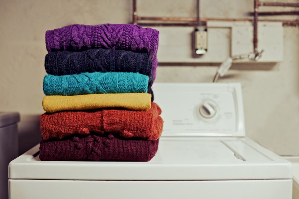 Sweaters stacked on a washing machine
