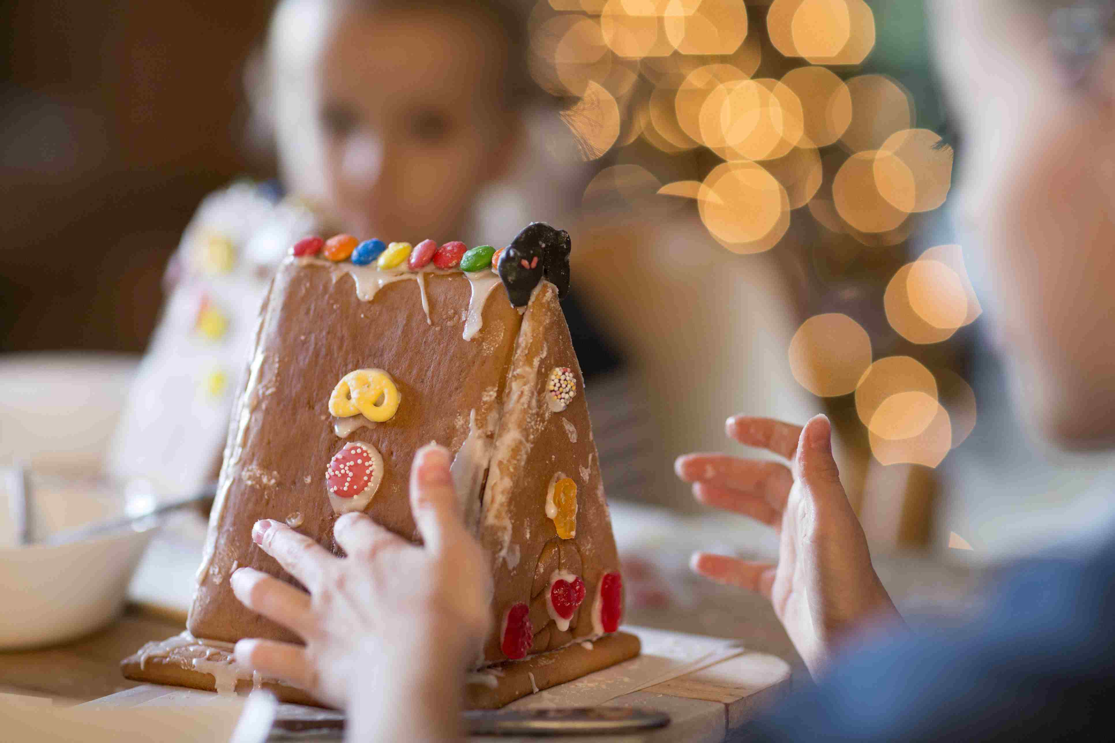 Children decorating gingerbread house
