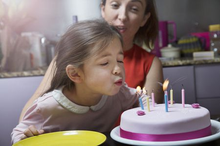 A Picture Of Child Blowing Out Candles On Cake