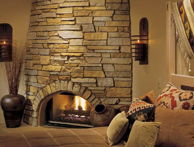 Classic Cleft stone fireplace with floor pillows and two candle sconces.