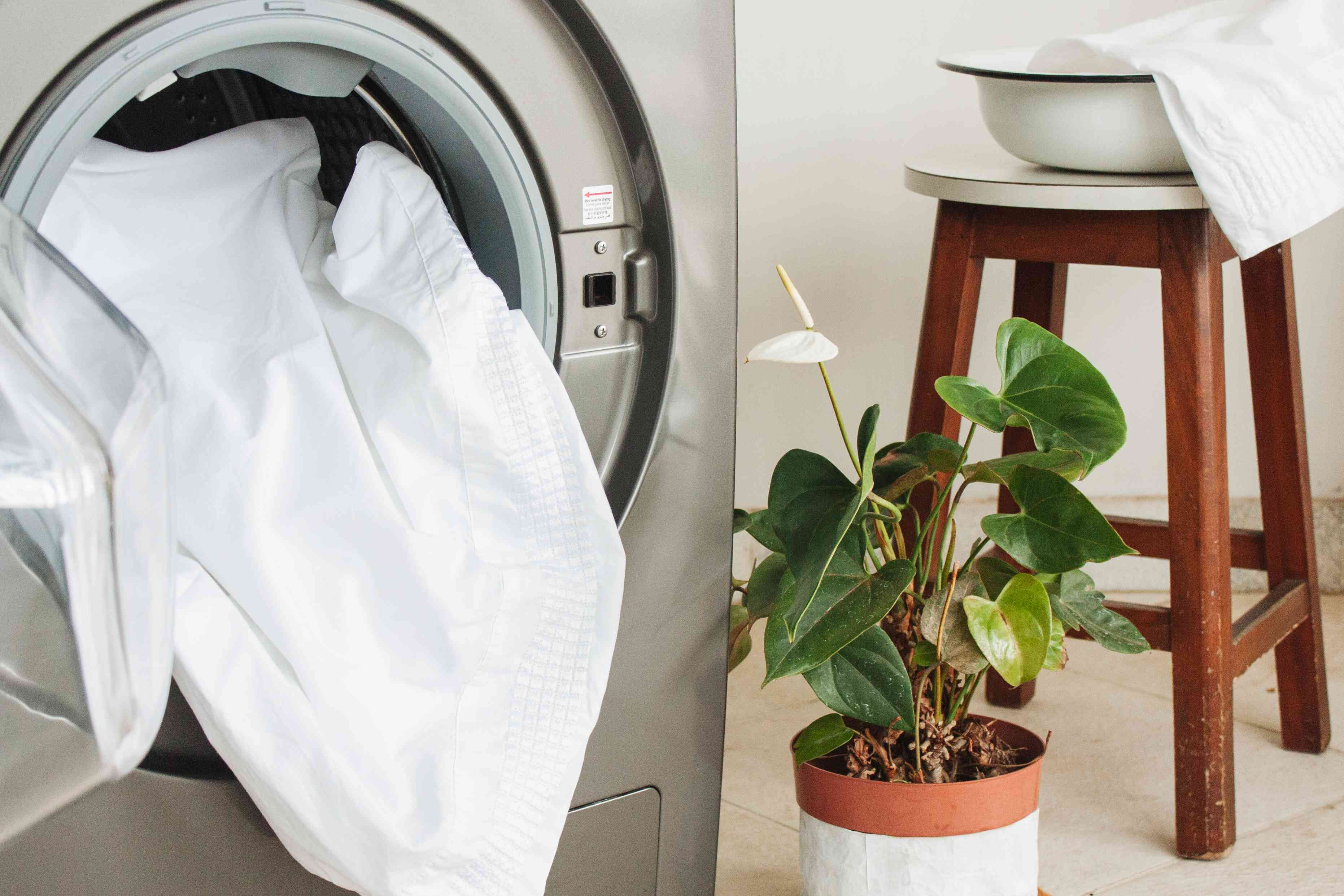 putting dirty bed linens into the washing machine