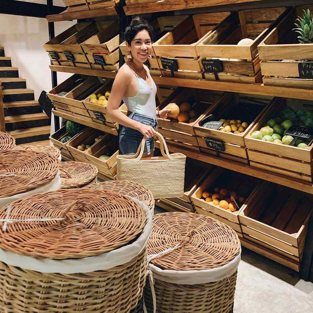 A woman standing among baskets and wooden crates of food with a basket in her hand
