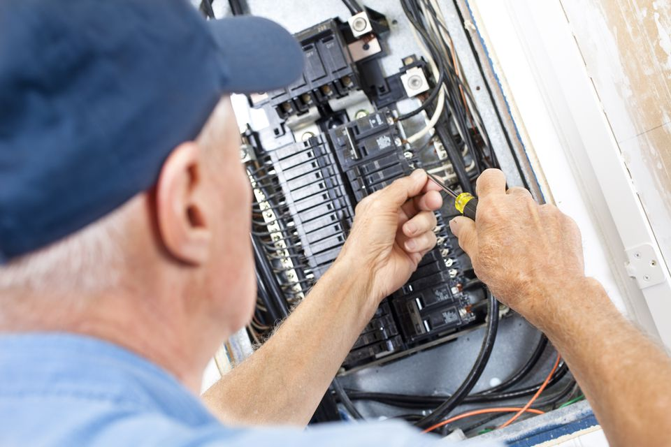 Man servicing main breaker panel