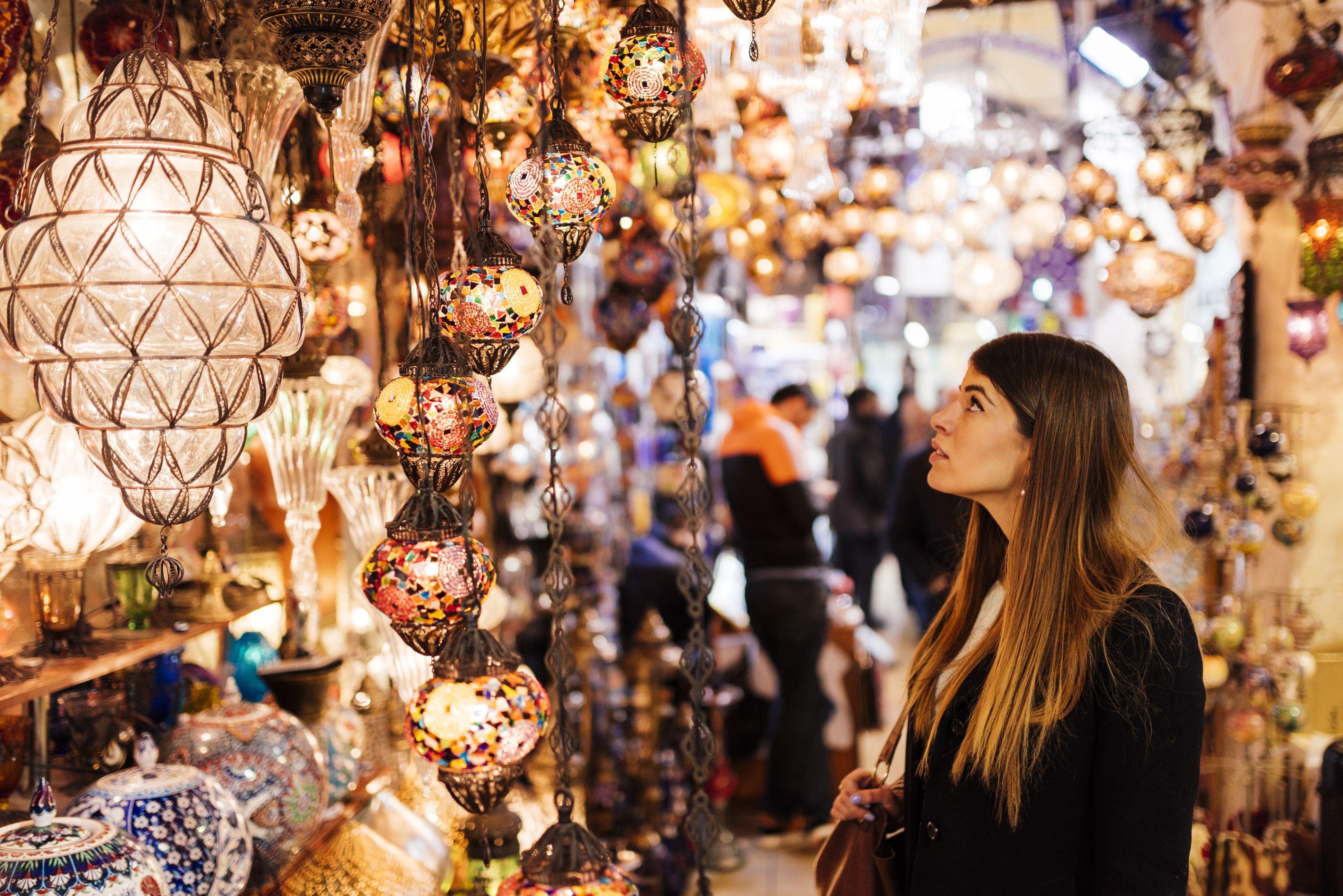 Mujer joven mirando las luces en el puesto del mercado