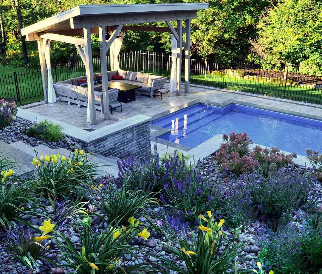 Terraced flower beds above a pool and a gazebo-style shelter