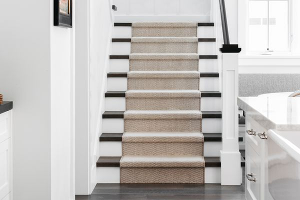 Staircase with white and brown steps lined with tan carpet runner in the middle