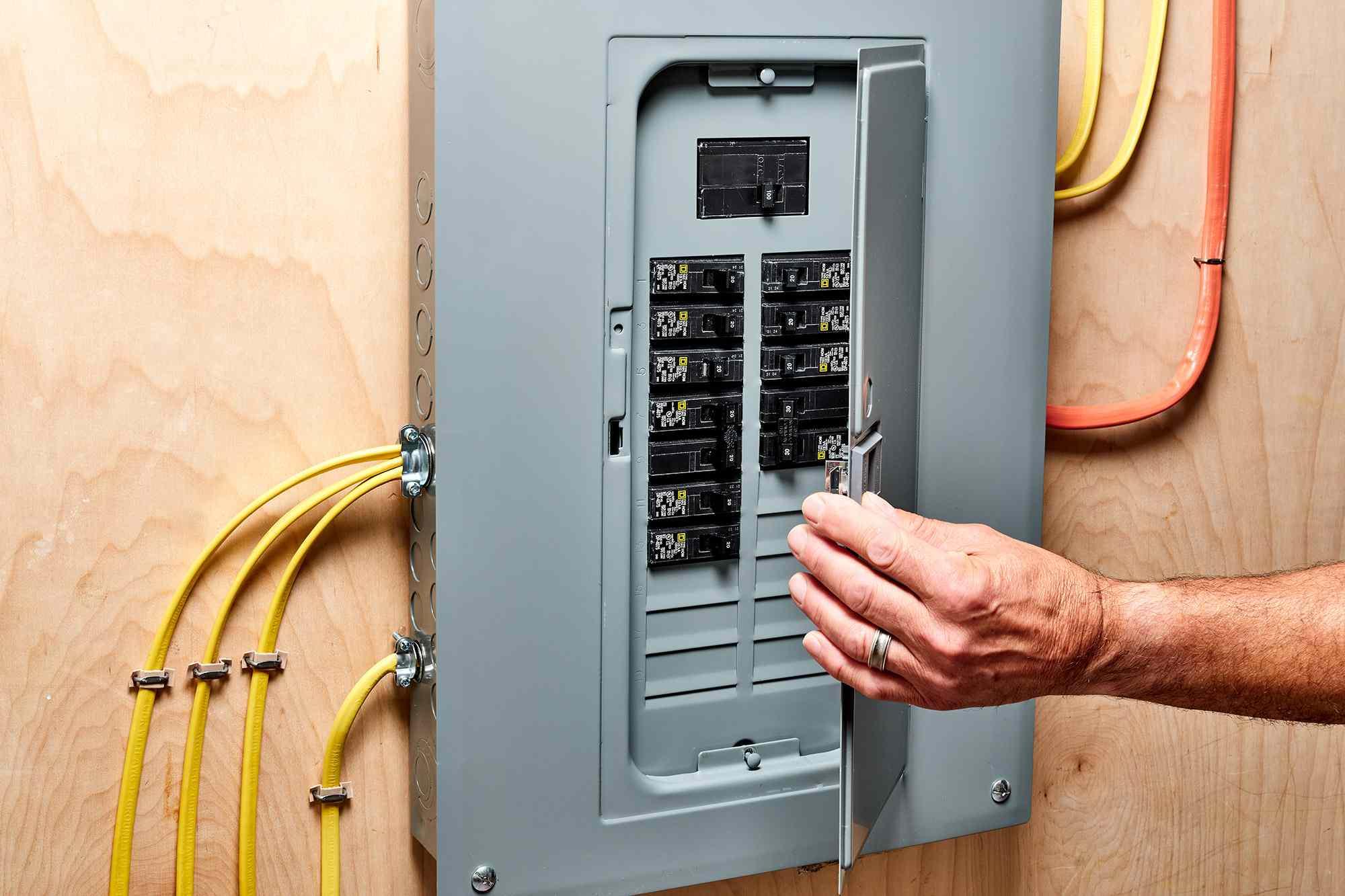 Gray metal service box with door open showing circuit breakers