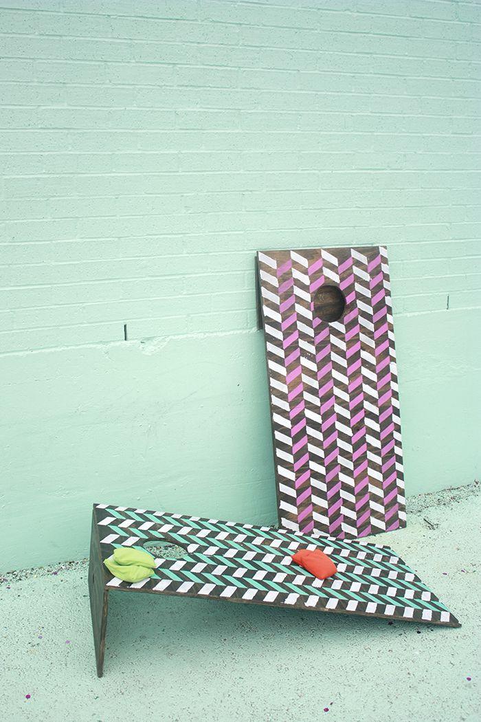 Two cornhole boards against a concrete wall