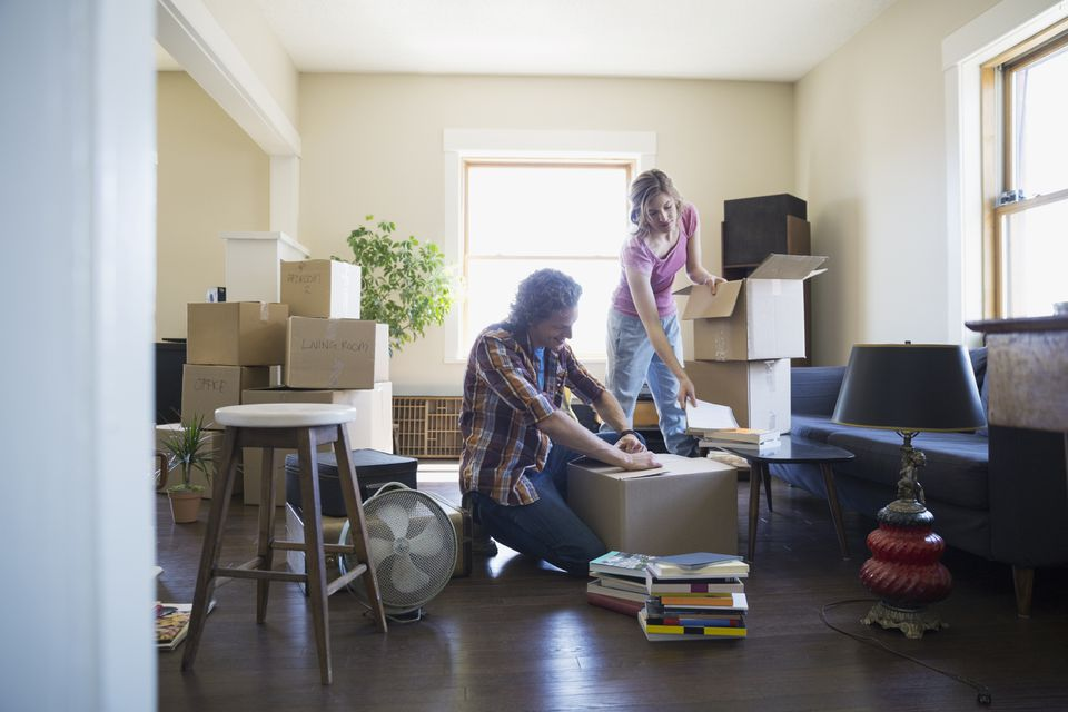 Couple packing moving boxes in living room